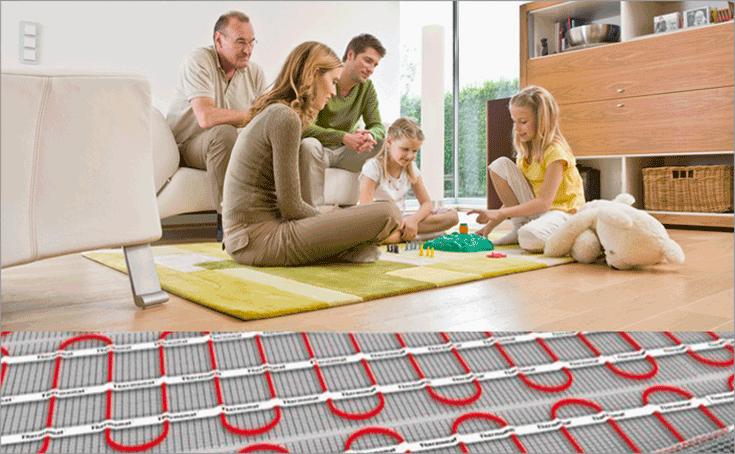 Семья сидит на полу в комнате. Схематически показано что под напольным покрытием есть электрический теплый пол.