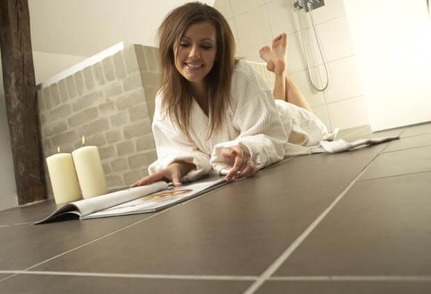 Девушка в ванной на полу из плитки, в халате читает журнал. Левее девушки зажжены две свечи. Теплый пол своими руками готов.