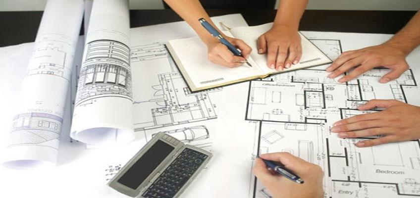 На столе чертежи, руки троих человек. Один размечает чертеж, другой пишет в блокноте, третий положил руки на чертеж. В стороне калькулятор.