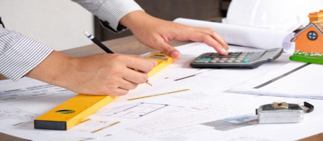Руки человека с калькулятором, карандашом и уровнем. Выполняется расчет теплого пола.