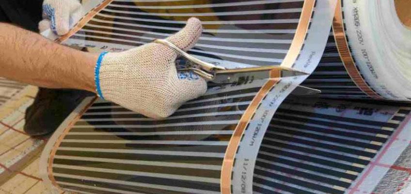 Рука человека режет ножницами инфракрасную пленку
