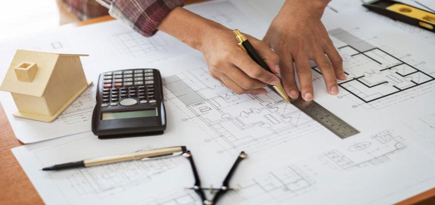 Руки человека с ручкой и линейкой на чертеже квартиры. В стороне калькулятор, штанген-циркуль и карандаш. Размечают размер теплого пола.