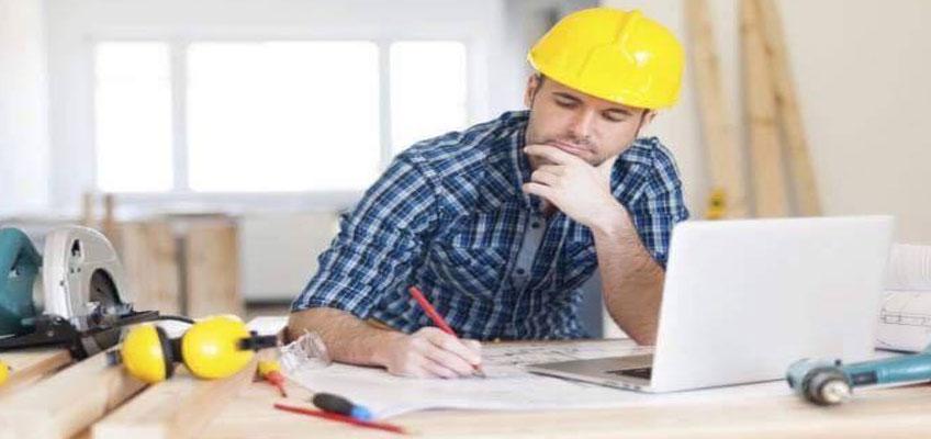 Специалист в желтой каске за столом, с карандашом в руках считает стоимость теплого пола.