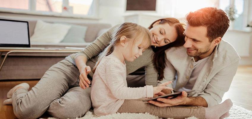 Родители и дочь сидят на полу