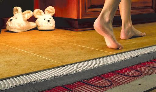 Участок пола. В разрезе показано устройство электрического теплого пола под плитку. Человек идет босиком по плитке.