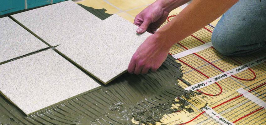 Участок пола. Человек укладывает керамическую плитку на плиточный клей поверх электрического теплого пола.