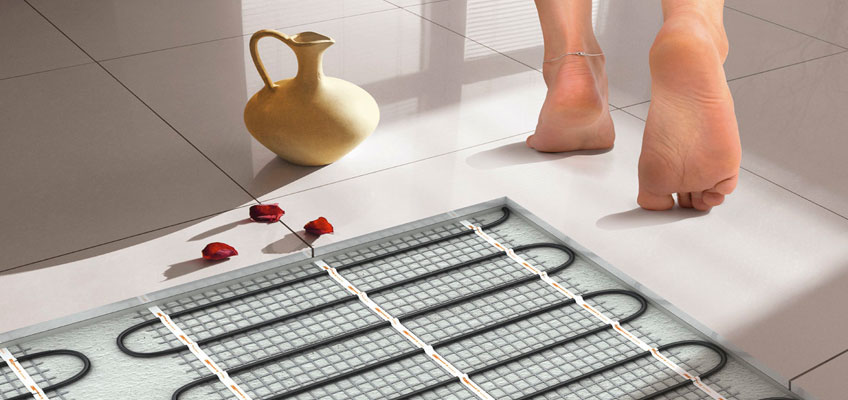 Электрический теплый пол - мат под керамической плиткой. Человек идет по плитке босыми ногами.