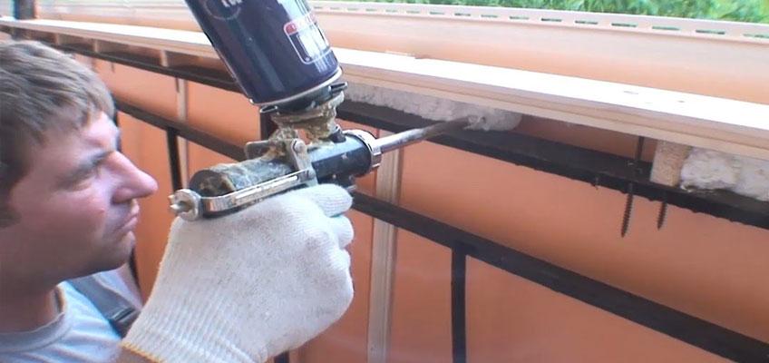Монтажник при помощи пистолета и баллона пены заполняет щели пеной.