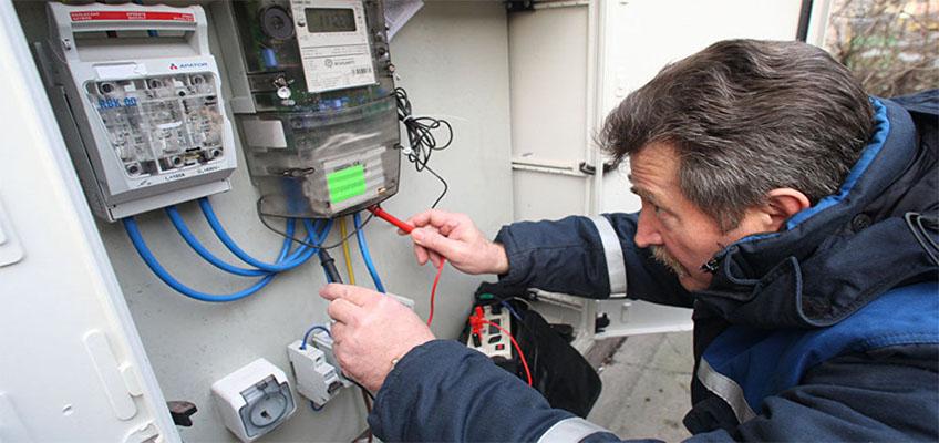 Электромонтажник проверяет потребление электроэнергии теплым полом