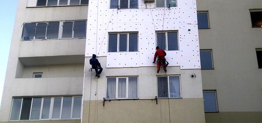 Высотники монтируют утепление на фасад многоквартирного дома.