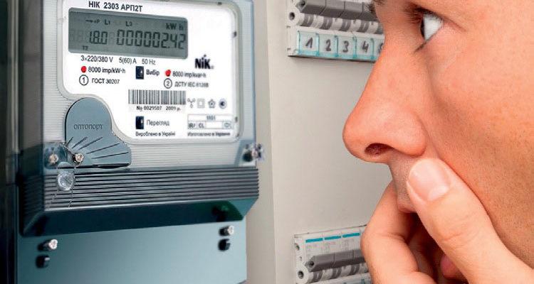 Человек смотрит на электросчетчик с удивлением. Он видит реальное потребление теплого пола.
