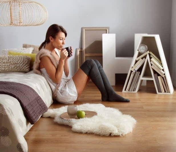 Девушка в спальне сидит на полу с чашкой кофе