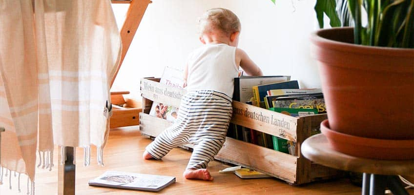 ребенок стоит босиком на полу в детской комнате, облокотившись на полку с книгами