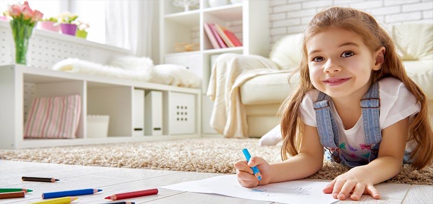 Девочка лежит на полу и рисует карандашами на бумаге