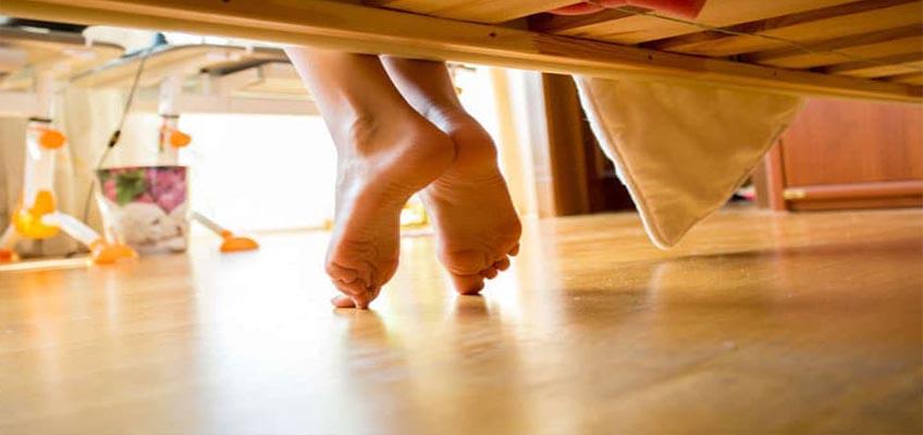 ноги свисают с кровати на ламинированный пол