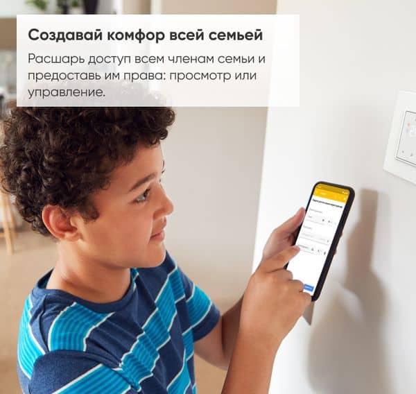 ребенок со смартфоном настраивает wifi регулятор теплого пола